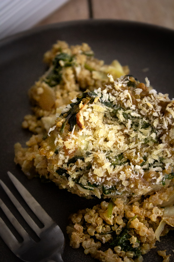A scoop of quinoa spinach bake on a gray plate with a fork.