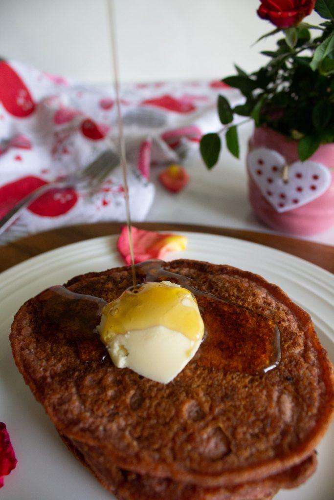 Beet red Valentine pancakes topped with vegan butter and maple syrup on a white plate with rose petals and red roses in the background.