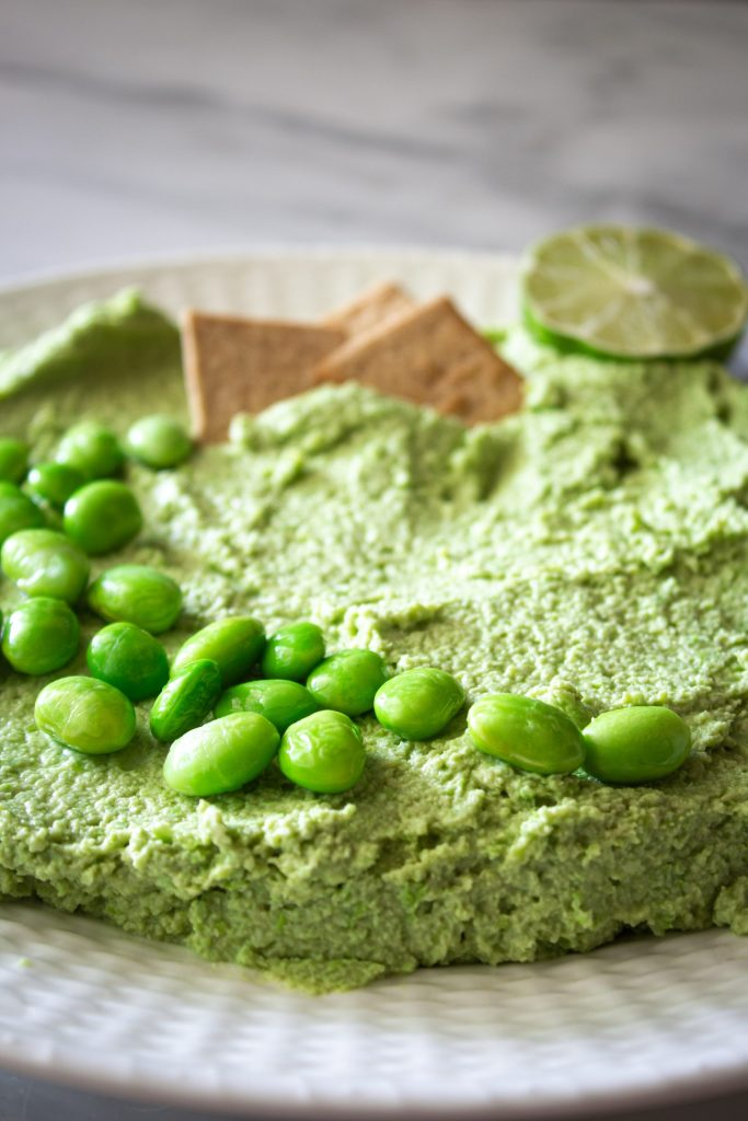 A white plate full of edamame hummus topped with edamame, chip, and a lime.