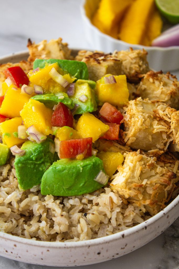 A bowl of coconut rice and coconut crusted tofu topped with mango avocado salsa with a while bowl of mango in the background.