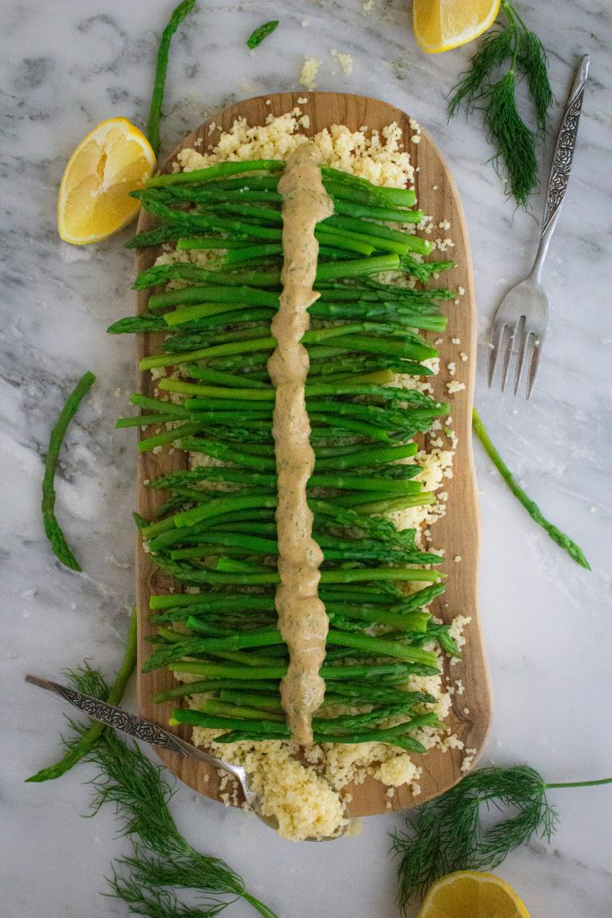 Whole-wheat couscous topped with asparagus and creamy lemon herb dressing on a wooden cutting board.