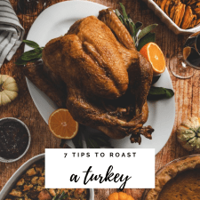 Overhead image of roasted turkey, surrounded by oranges and various side dishes, linking to article about Tips on how to roast the perfect turkey