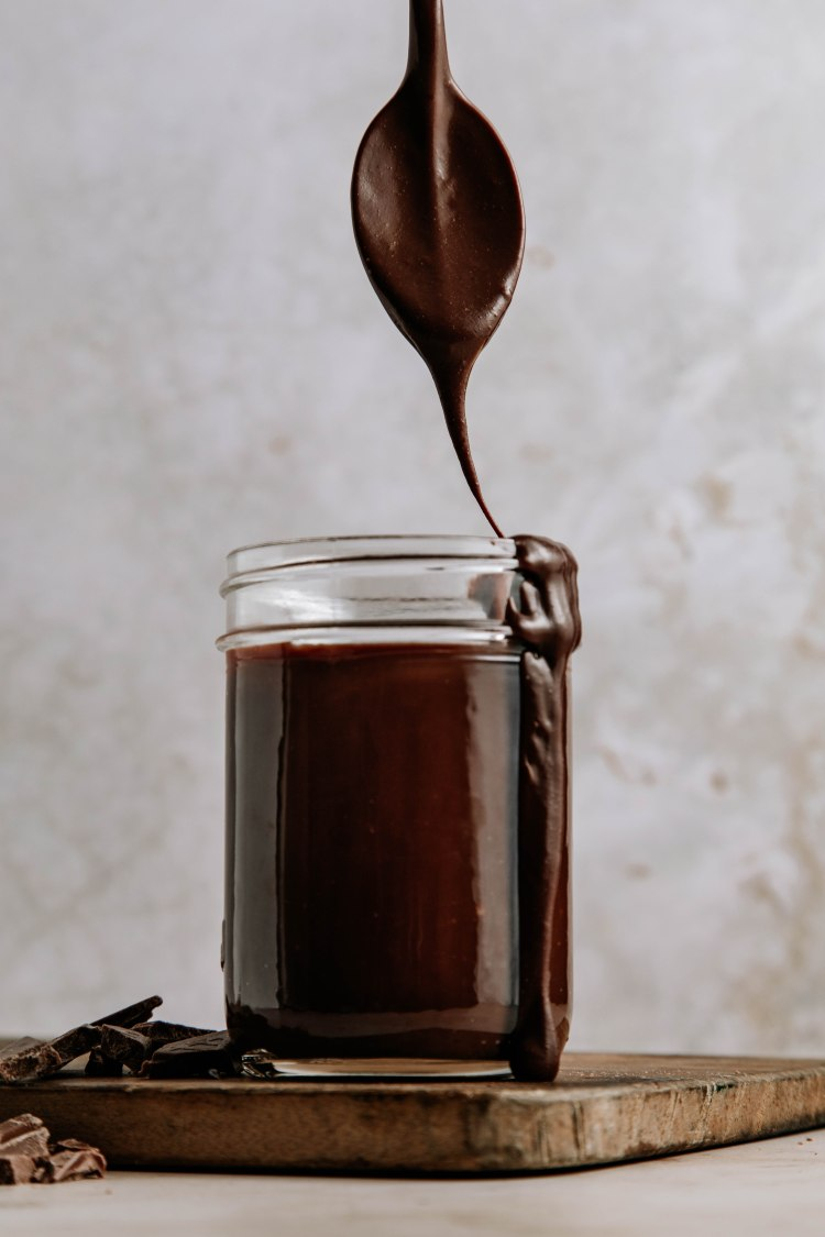 Spoon dripping chocolate ganache into jar by Cashmere & Cocktails