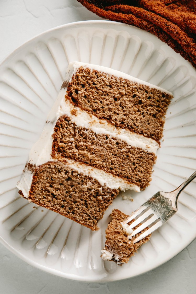 Over head image of a slice of spice cake with brown butter frosting on a plate, with a bite taken out of the bottom corner.