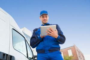 Low angle view of delivery man using digital tablet by truck against sky