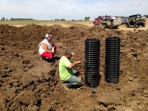 """John observes as Tyler Shepard drills """"portholes"""" into the large 15"""" riser.  This will be the new inlet for surface water drainage at the Burke farm."""