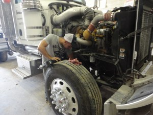Brandon greases the front end of the Peterbilt