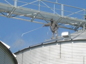 """Robert (aka """"Spiderman"""") applies the shiny aluminum paint to the roof of bin #10A."""