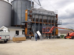 The crew from MAS install some new stainless steel perforated panels to the skin of the GSI 2326 grain dryer.
