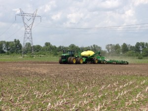 """I stepped out to observe while Nicolas experienced the AutoTrac.  Notice the bare ground around the tractor where the heavy rain stood and stopped the original planting of soybeans.  We """"filled in"""" the gaps today.  We still had some tiny patches of water to drive around even today!"""
