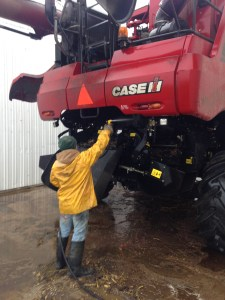 Here, Brandon washes the mud from the undercarriage of the CIH 8230 combine.  After this, the 'skin' of the machine can be washed inside the shop.