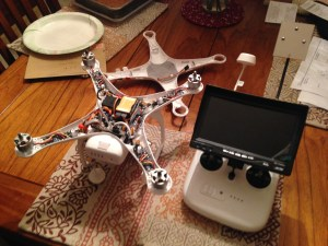 Here you see the Phantom 2 with the propellers and top cover removed.  A pretty complex little machine.  On the right is the FPV attached to the control box.