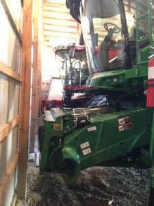 The combines are nosed in to the back wall of the storage barn.