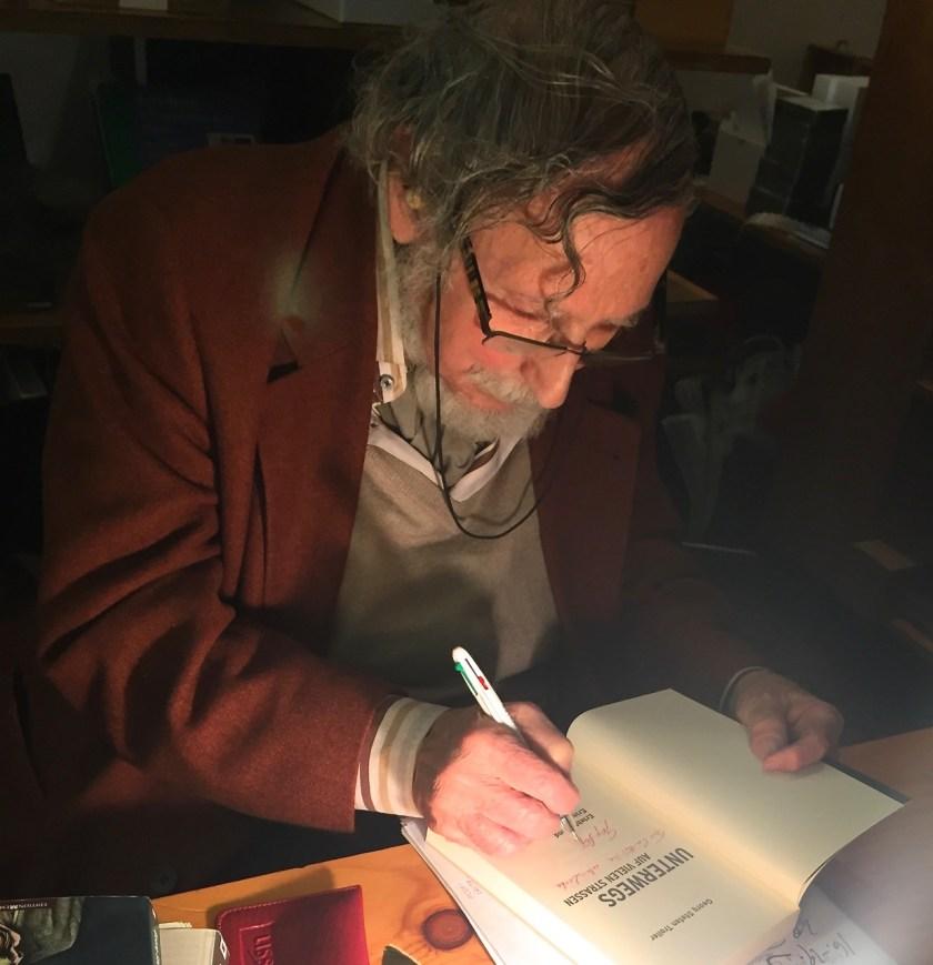 """Georg Stefan Troller signiert sein Buch """"Unterwegs auf vielen Straßen"""""""