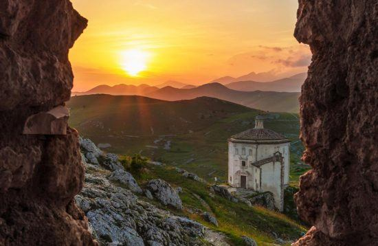 sunset on top of a mountain in Abruzzo viewed from a rock window