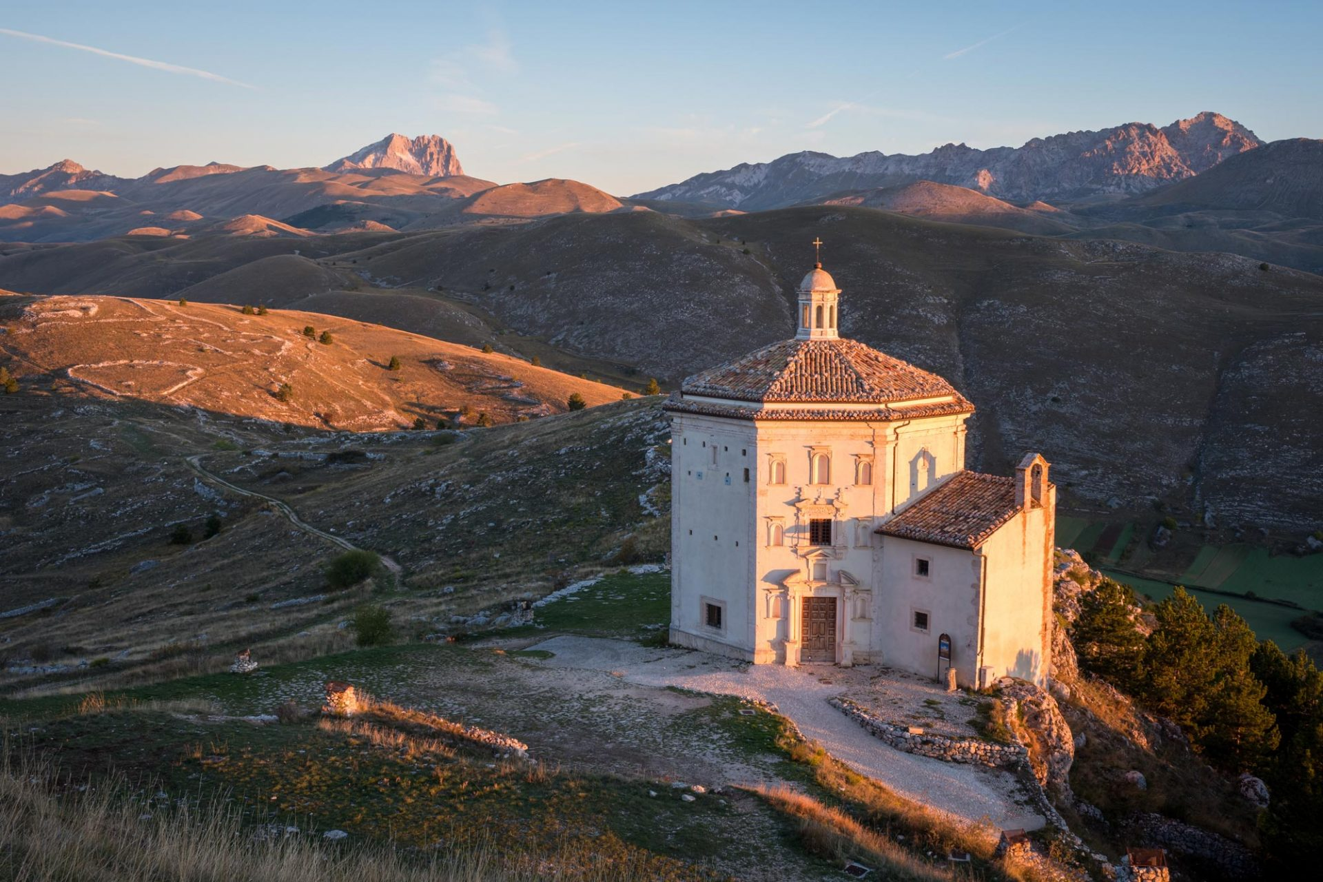 church built on a mountain in italy at sunset