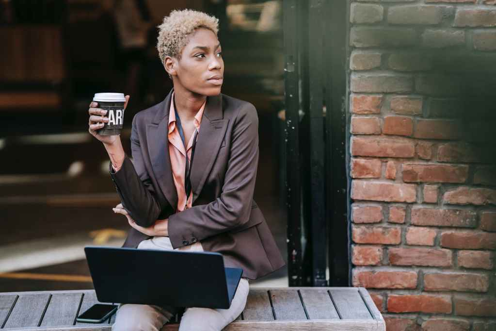 pensive young black woman sitting on street bench with laptop during coffee break
