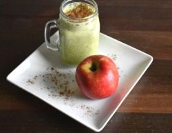 Mug of apple pie protein shake with an apple