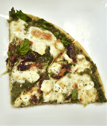 chickpea crust pesto pizza topped with sun dried tomatoes and feta