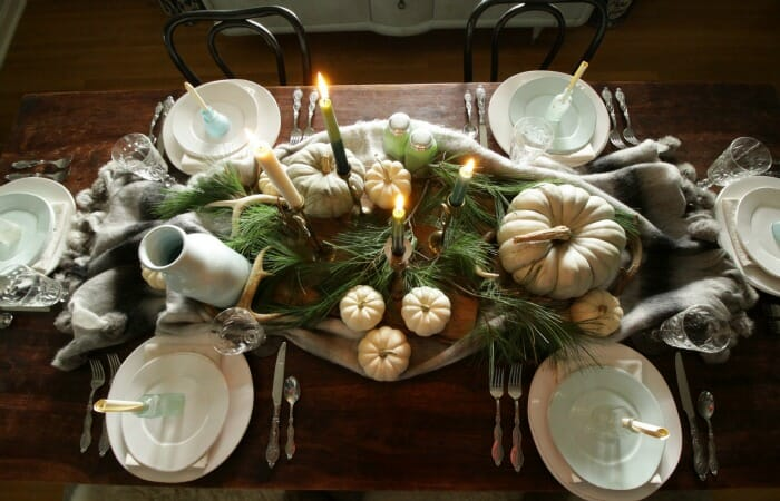 Thanksgiving table in blues and greens with pine and pumpkins