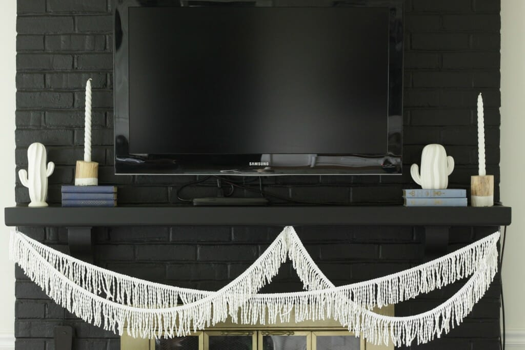 Simple Modern Boho Mantle with White Cactus, Fringe, Books, and Candlesticks