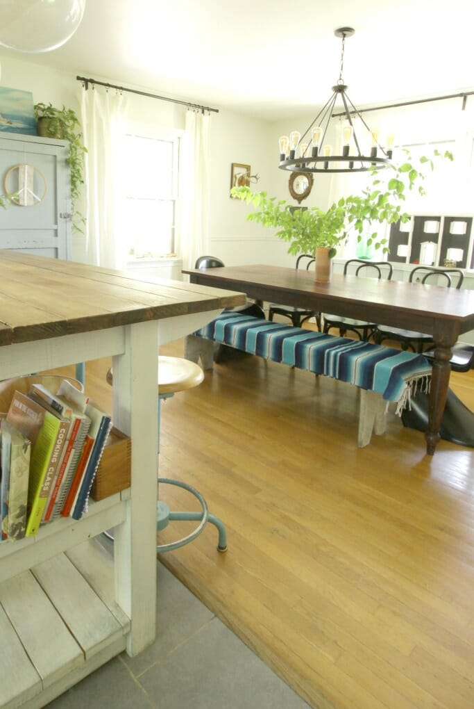 Eclectic Dining Room with Sarape on bench, industrial island dividing spaces
