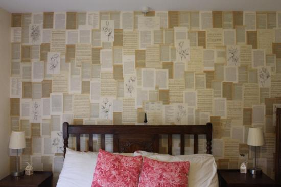 DIY wallpaper for bedroom makeover using pages from old books and sheet music