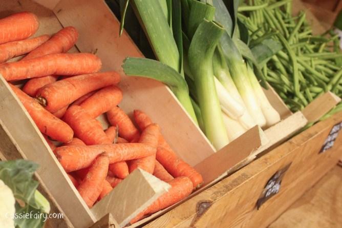 Farm shop produce on shelves, including carrots, leeks and beans