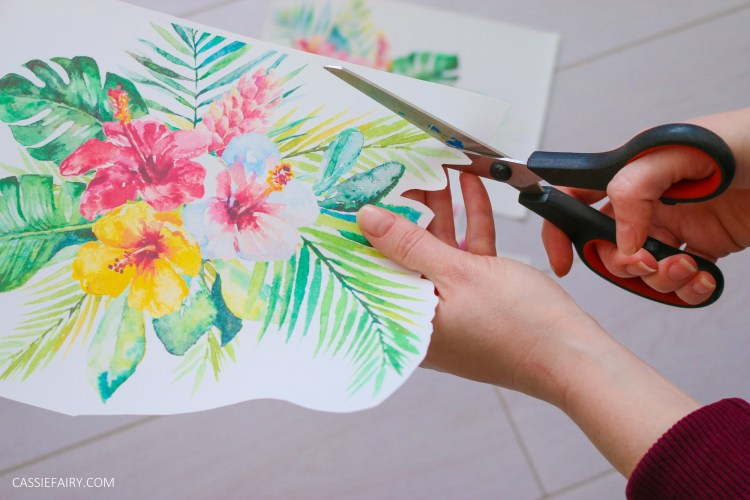 Iron-on transfer paper printed with a tropical design, being cut out around the leaves.