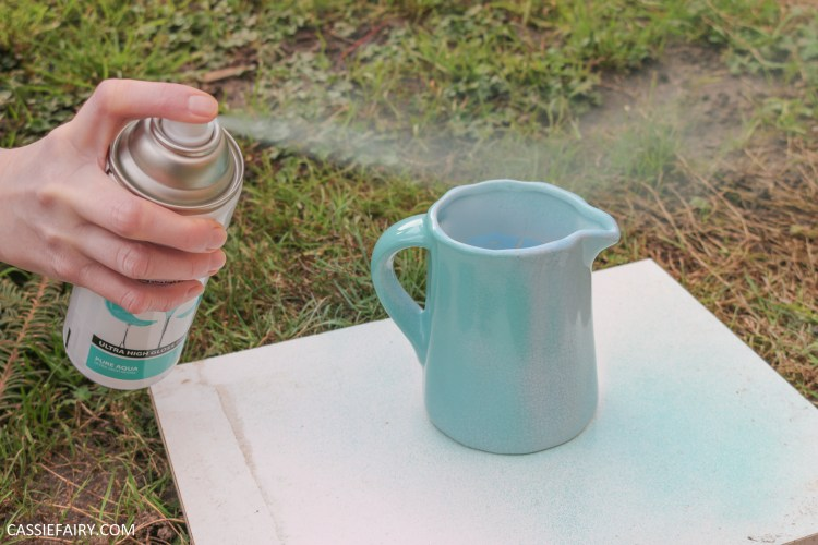 spray painting a small jug with turquoise paint