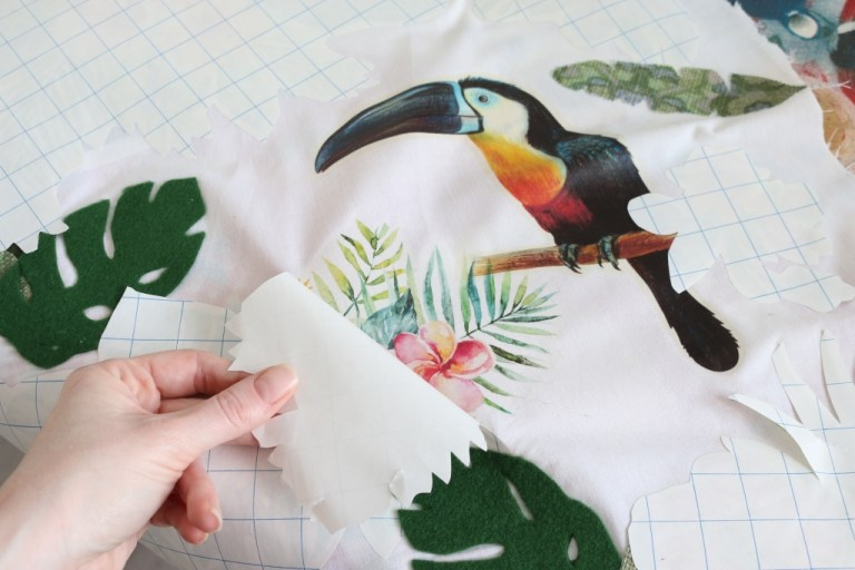 Iron-on transfer backing paper being peeled away from a transferred image