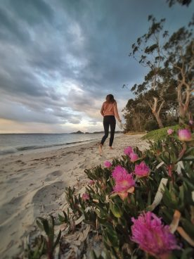 A girl walks across the beach in Nelsons Bay at sunset