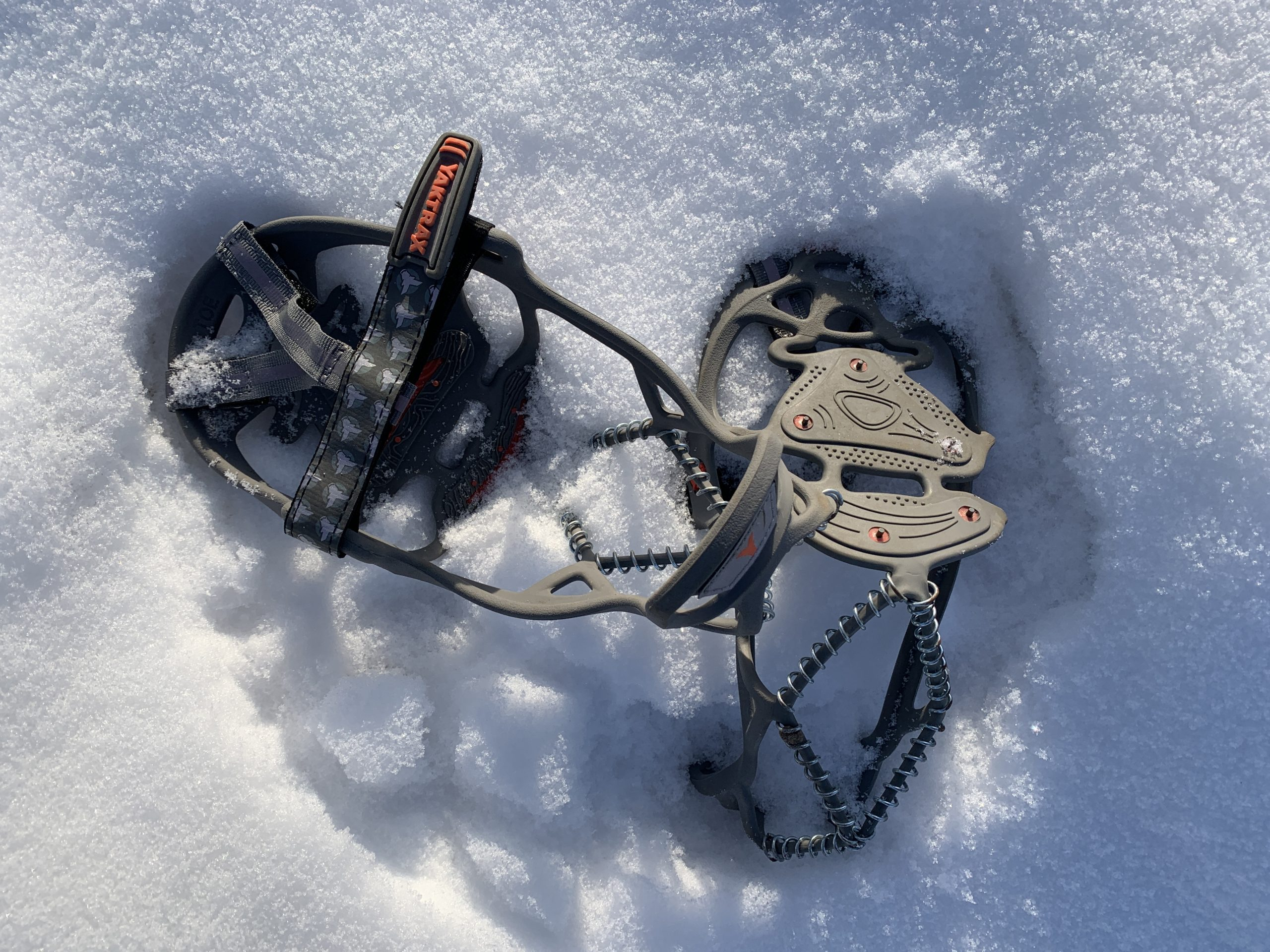 A pair of traction footwear strap-ons rest in fresh snow.