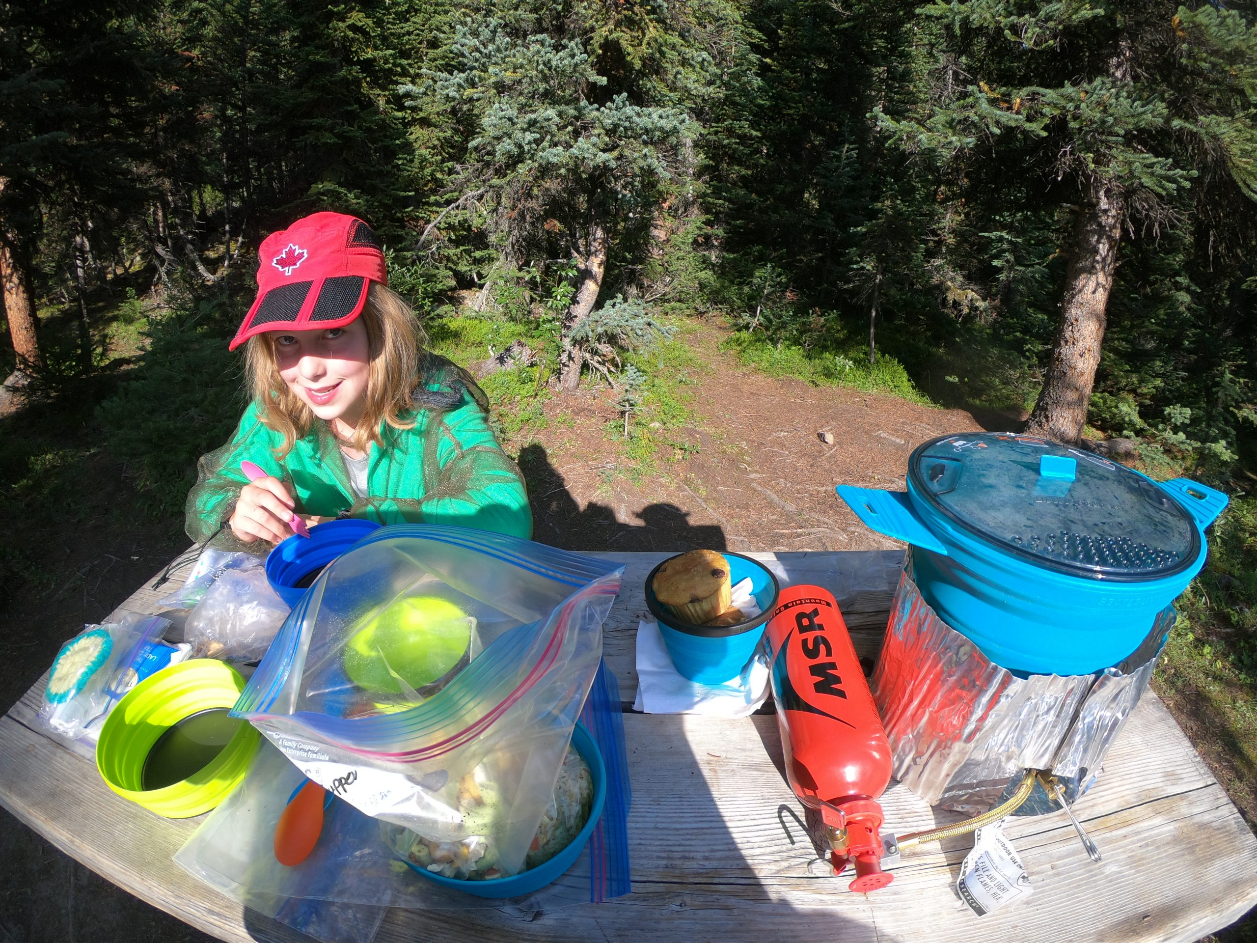 An elaborate backpacking camp stove and fuel bottle is set up on small table.