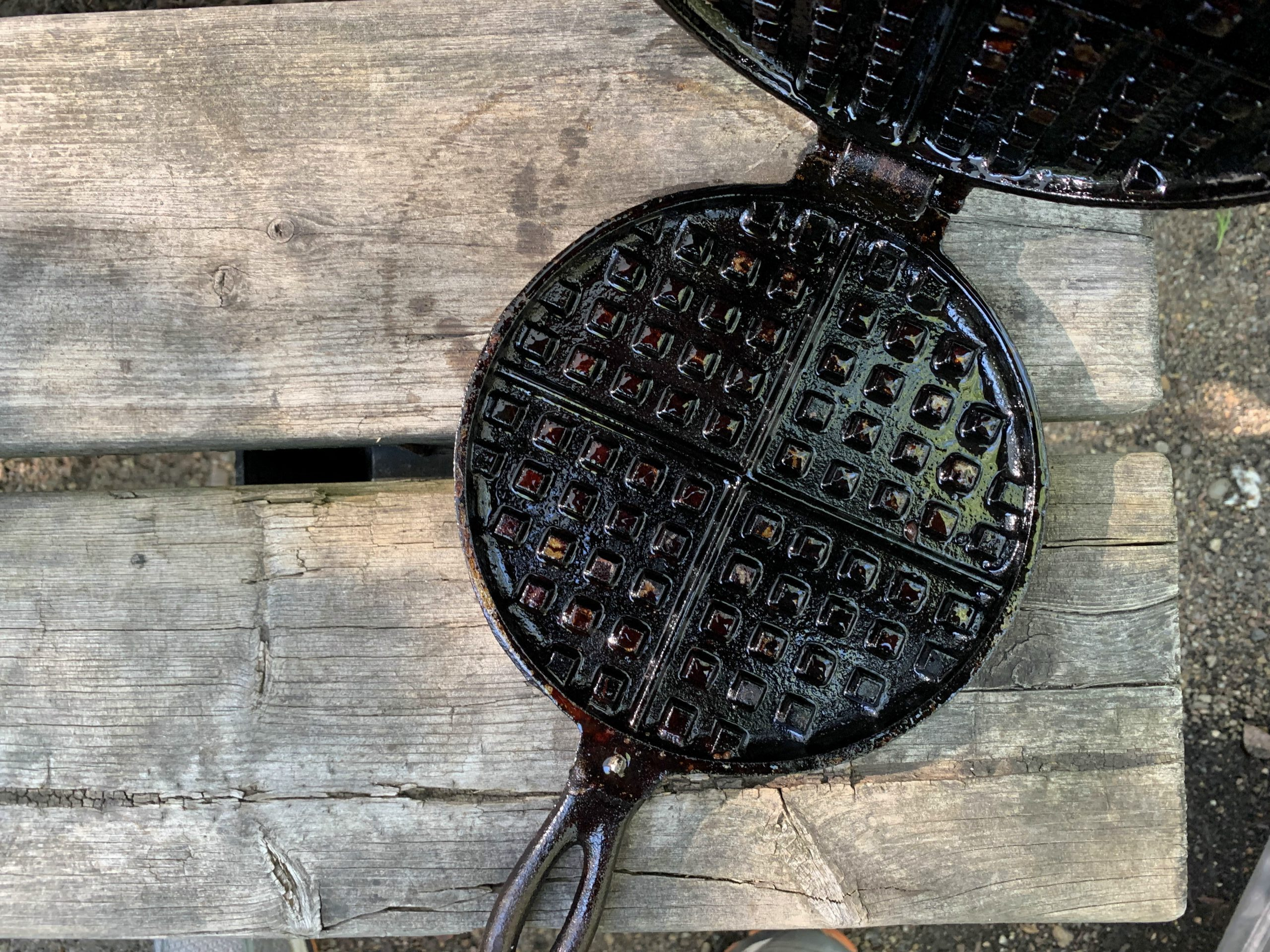 A small cast iron waffle pan open on a picnic table.