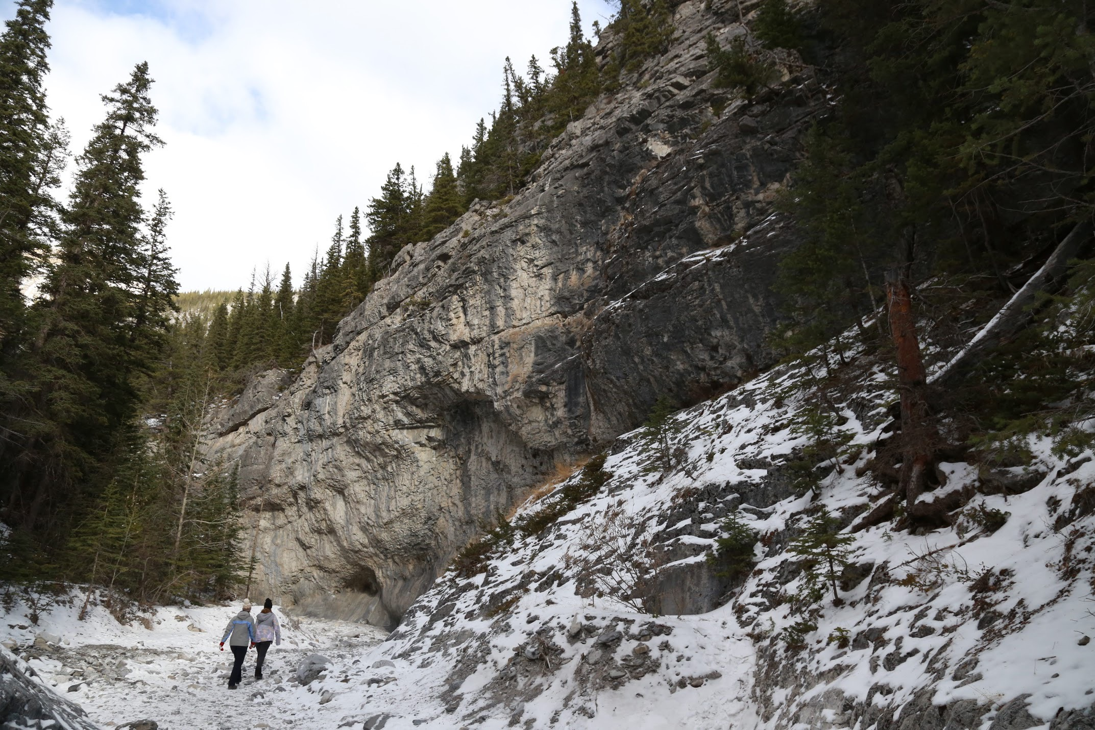 A snowy mountain canyon with two figures hiking deeper into the trail.