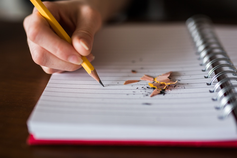 a hand holds a pencil to a blank page, ready to write