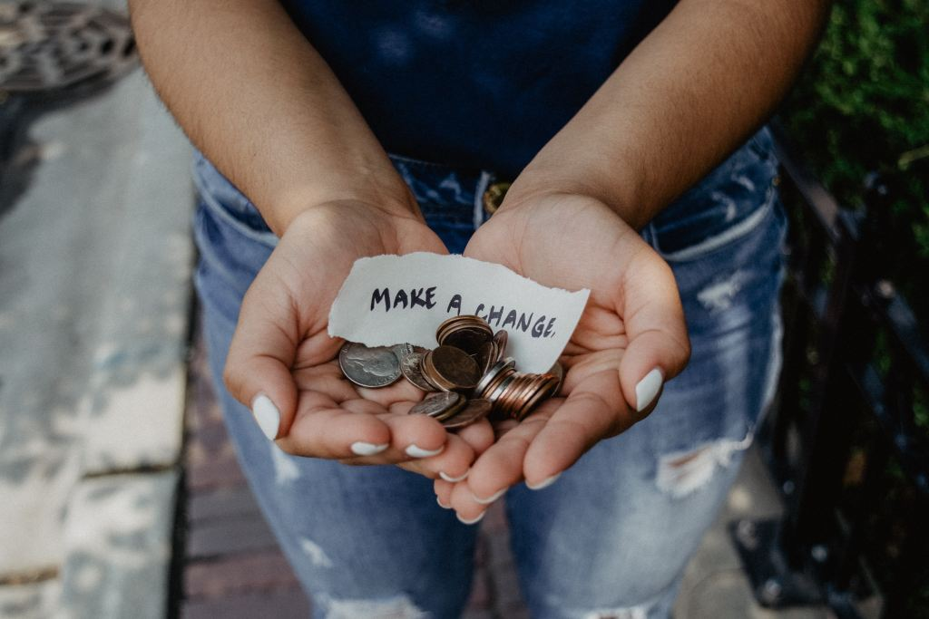 a pair of hands put together, filled with coins and a piece of paper that says