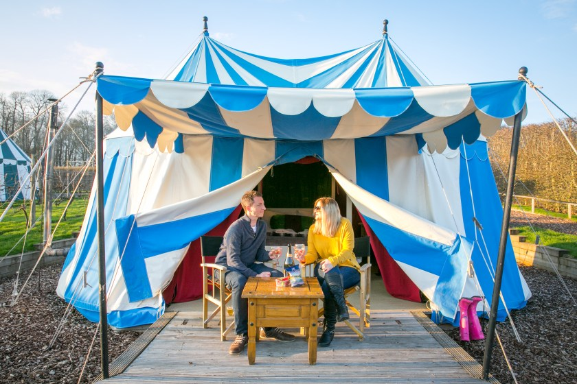 A couple sitting outside their tent at Leeds Castle