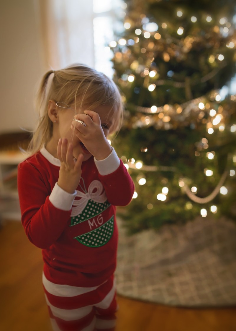 toddler with christmas tree decorating christmas pajamas