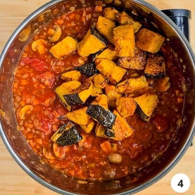 Roasted pumpkin pieces added into pot of vegetable sauce