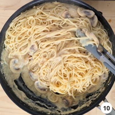Pasta being tossed and mixed into creamy mushroom sauce with a pair of tongs