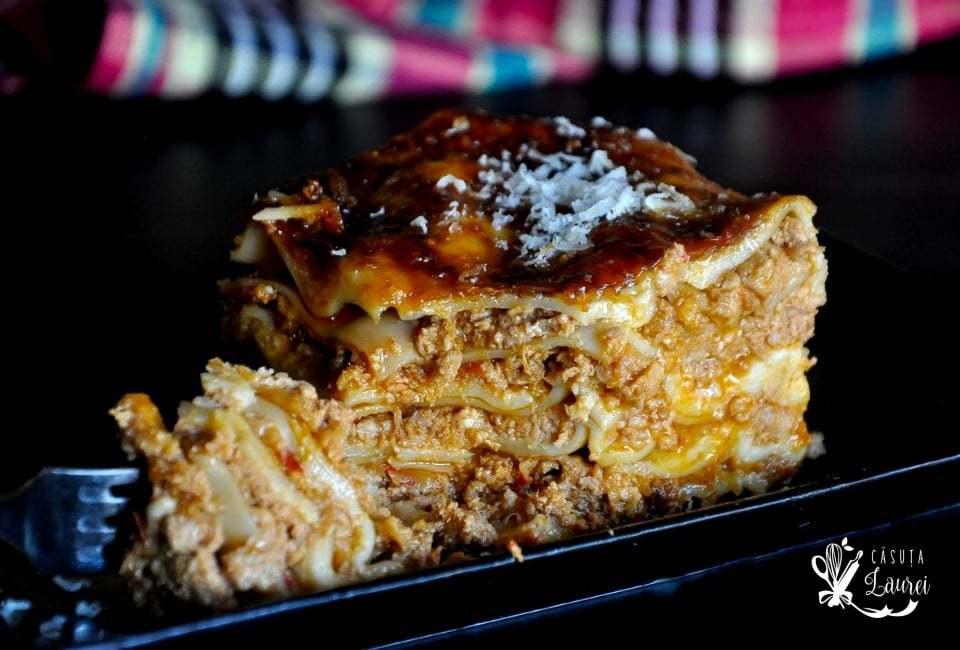 lasagna bolognese servita pe o farfurie neagra