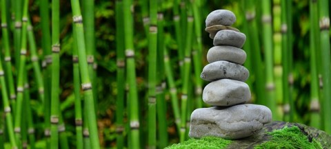 zen garden with bamboo in the background and stacked zen stones in the foreground