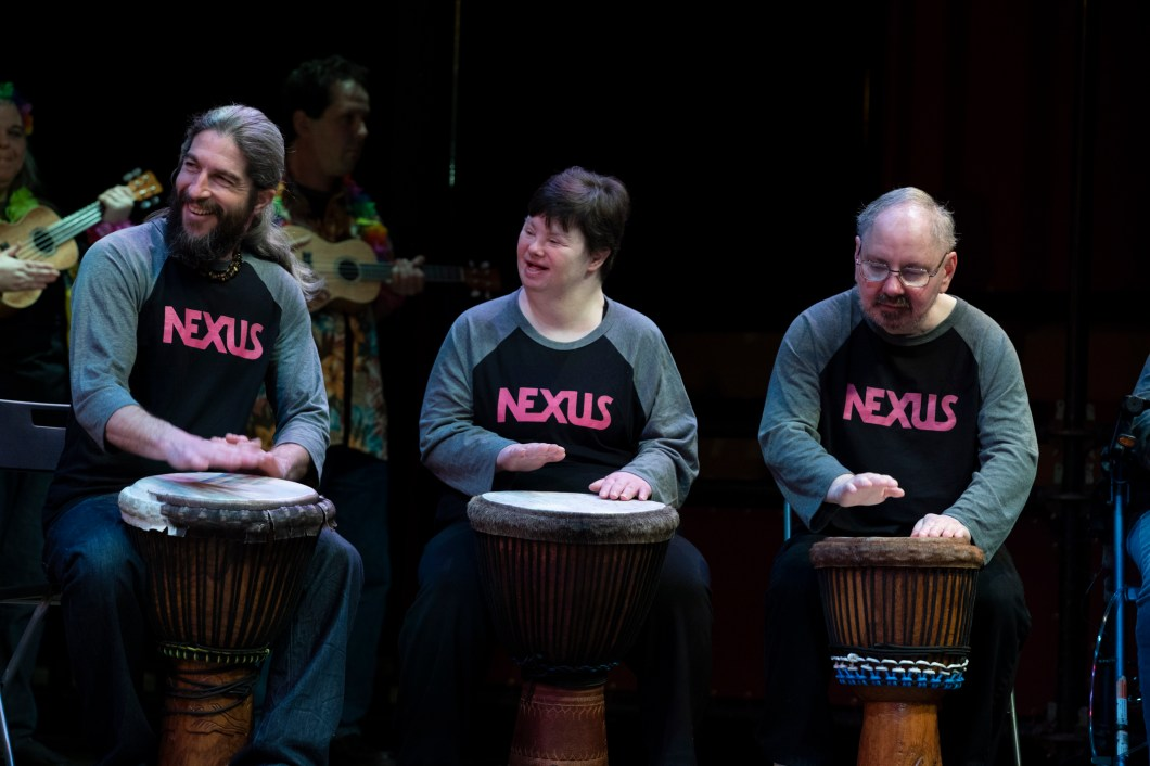 "Three people sit in a row playing drums. They are on stage, smiling, each wearing a shirt that says ""Nexus"""
