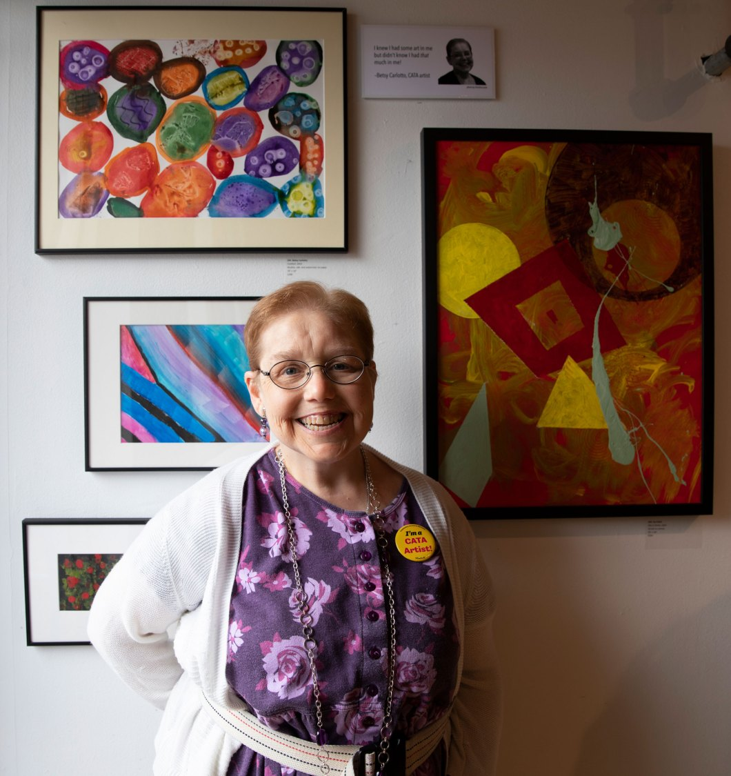 Betsy Carlotto stands smiling in front of her painting on display on an art gallery. She is wearing a purple dress and a white cardigan. Her painting, on the wall above her, features multicolored round stone-like shapes.