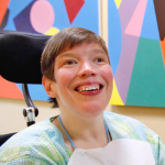 White woman in a wheelchair wearing a light blue and green shirt, smiling.