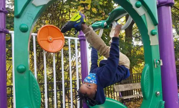 Catalyst scholar spinning upside down on the playground, wearing a mask