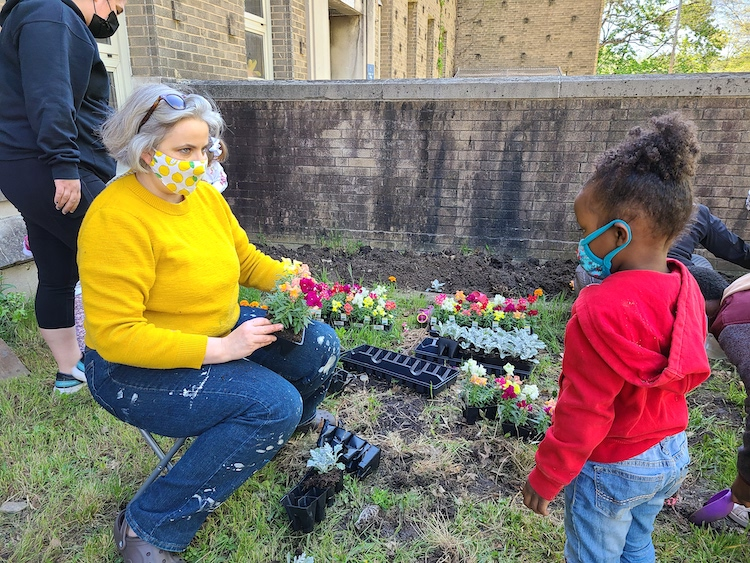 Catalyst Academy teacher with student planting garden