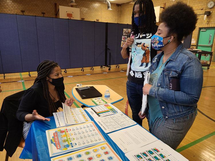 Catalyst teacher talking with parents at a Meet & Greet event